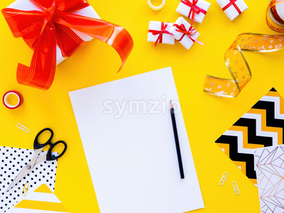 Table with things for preparing gifts, gift boxes, tapes, stationery. Yellow background. Holiday concept. Top view Stock Photo