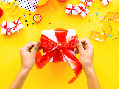 Female hands hold a gift box, decoration around on yellow background. Holiday concept. Top view Stock Photo