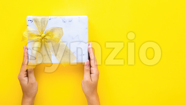 Female hands hold a gift box on yellow background. Holiday concept. Top view Stock Photo
