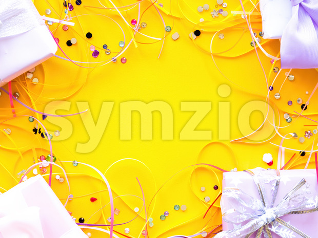 Few gift boxes with tapes and decoration around on yellow background. Holiday concept. Top view