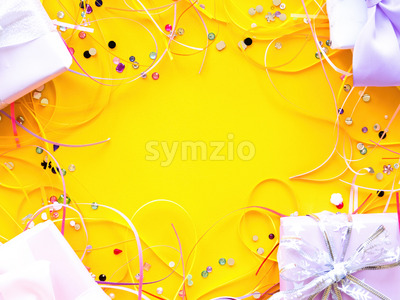 Few gift boxes with tapes and decoration around on yellow background. Holiday concept. Top view Stock Photo