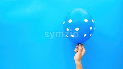 Female hand holds a balloon with white circles on blue background. Holiday concept. Top view Stock Photo