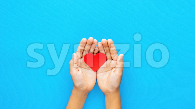 Man hands holds a red heart on blue background. Love concept. Top view