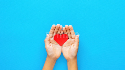 Man hands holds a red heart on blue background. Love concept. Top view Stock Photo