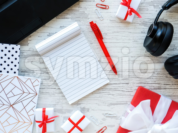 Table with things for work, gift boxes, note book, headphones, laptop, stationery. Work concept. Top view Stock Photo