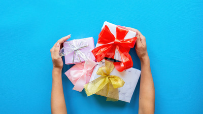 Female hands hold few gift boxes on blue background. Holiday concept. Top view Stock Photo