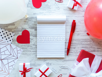 Table with gift boxes, note book, stationery, red hearts, balloons. Love letter concept. Top view Stock Photo