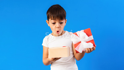 A caucasian child is surprised with a gift box. Blue background. Holiday concept. Front view Stock Photo