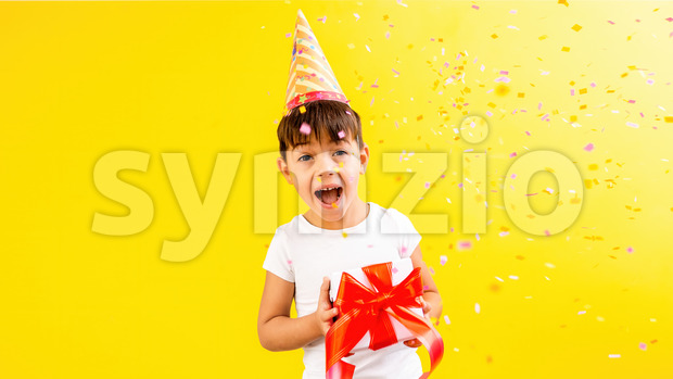 A caucasian child in holiday cap is happy with a gift box, confetti. Blue background. Holiday concept. Front view Stock Photo