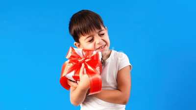 A caucasian child is pleased with a gift box. Blue background. Holiday concept. Front view Stock Photo