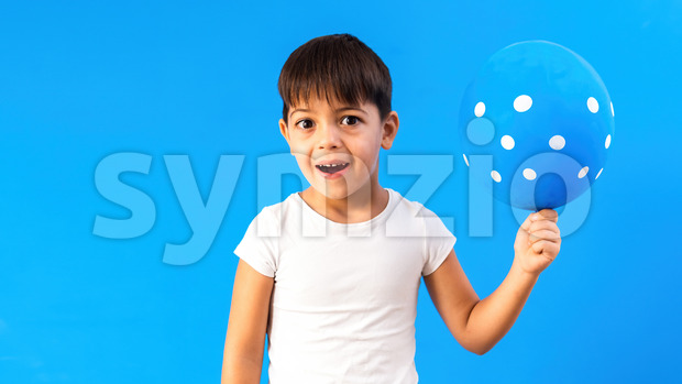A caucasian child is happy with a balloon with white circles. Blue background. Holiday concept. Front view