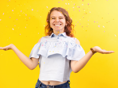 Happy smiling caucasian woman with confetti around in the air, yellow background. Holiday concept. Front view Stock Photo