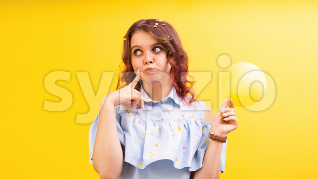 Thinking caucasian woman with a balloon in one hand, yellow background. Holiday concept. Front view Stock Photo
