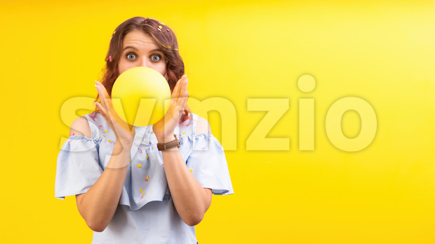 Surprised caucasian woman with a balloon between two hands, covering face, yellow background. Holiday concept. Front view Stock Photo