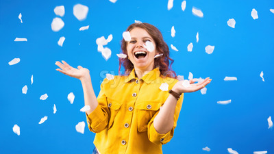 Happy smiling caucasian woman with confetti around in the air, blue background. Holiday concept. Front view Stock Photo