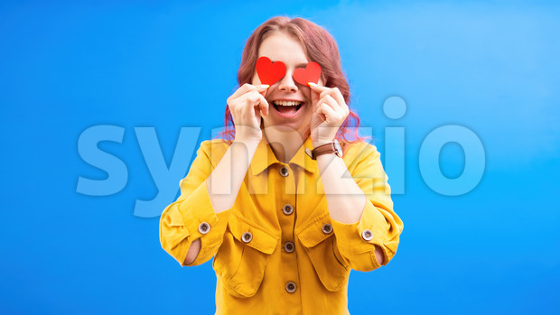 Happy smiling caucasian woman with two red hearts in hands, covering eyes, blue background. Love concept. Front view Stock Photo