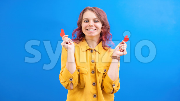 Happy smiling caucasian woman with two red hearts in hands, blue background. Love concept. Front view Stock Photo