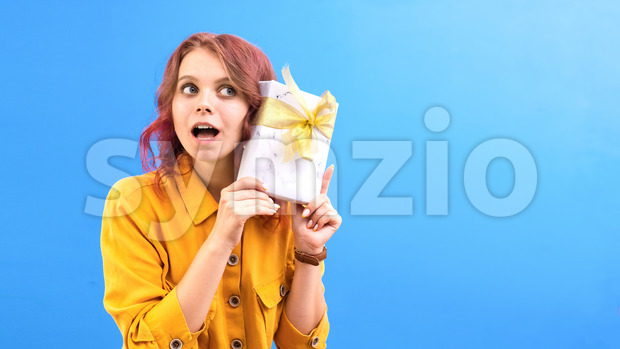 Thinking surprised caucasian woman with a gift box in hands near the head, blue background. Holiday concept. Front view Stock Photo