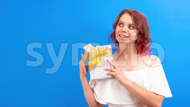 Thinking surprised caucasian woman with a gift box in hands, blue background. Holiday concept. Front view Stock Photo