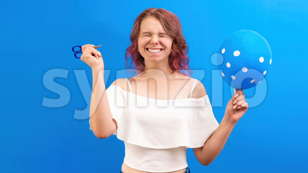 Thinking surprised caucasian woman with closed eyes, with a balloon and scissors in hands, preparing to blow, blue background. Holiday concept. Front Stock Photo
