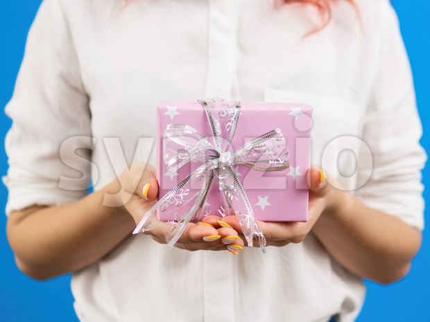 Female holds a gift box on blue background. Holiday concept. Front view Stock Photo