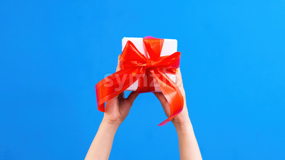 Female hands hold a gift box with red tape on blue background. Holiday concept. Front view Stock Photo