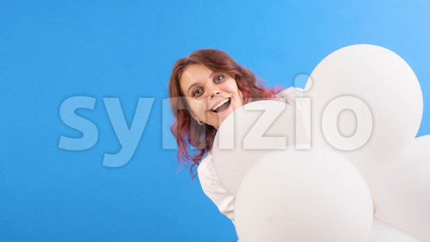 Happy smiling caucasian woman with white balloons looking out from behind them, blue background. Holiday concept. Front view Stock Photo