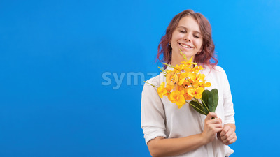 Pleased smiling caucasian woman with flowers and closed eyes, blue background. Holiday concept. Front view Stock Photo
