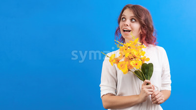 Thinking smiling caucasian woman with flowers and closed eyes, blue background. Holiday concept. Front view Stock Photo