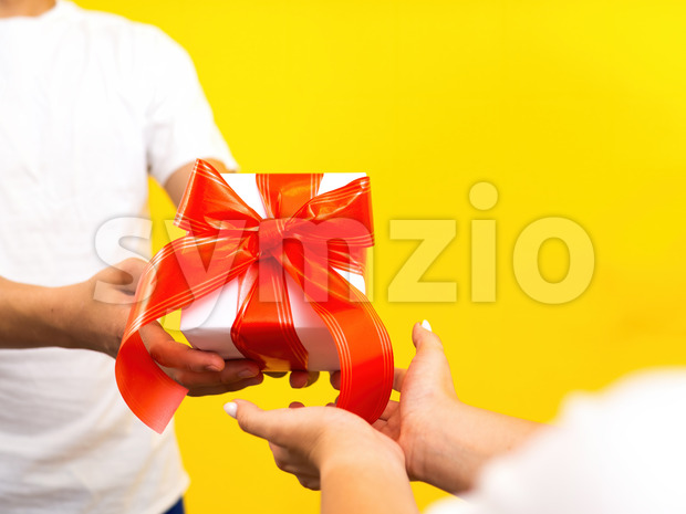 Man giving a gift box with red tape to a woman on yellow background. Hands. Love concept.