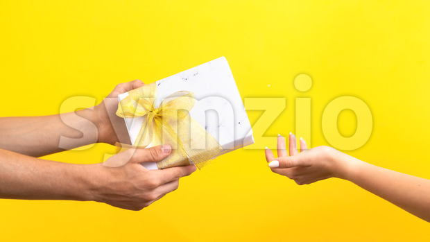 Man giving a gift box with red tape to a woman on yellow background. Hands. Love concept. Stock Photo