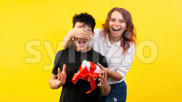 Smiling woman surprising a boy with a gift box with red tape closing his eyes, yellow background. Holiday concept Stock Photo