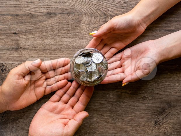 Transfer of the can with metal coins from man to woman , people hands. Wooden background. Top view Stock Photo