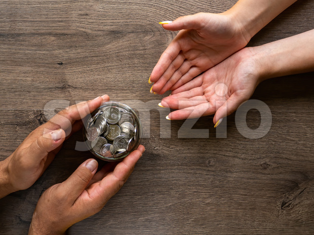 Man giving a woman the can with metal coins, people hands. Wooden background. Top view Stock Photo