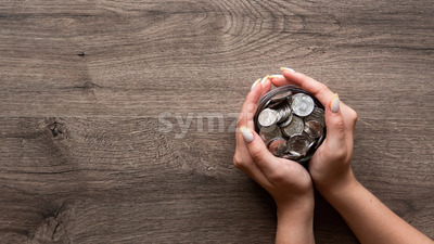 Woman is holding the can with metal coins. Woman hands. Wooden background. Top view Stock Photo