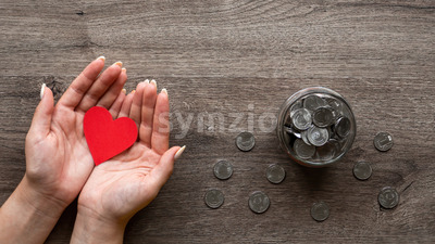 Woman is holding a red hearth, the can with metal coins inside and around it. Woman hands. Wooden background. Top view Stock Photo