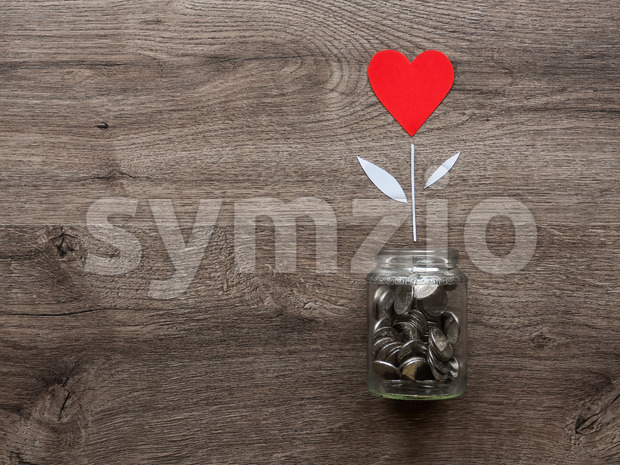 A glass can with metal coins and a flower with red heart growing up in it. Wooden background. Top view
