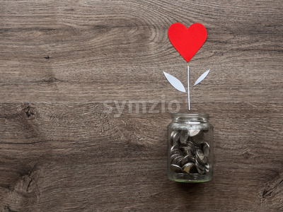 A glass can with metal coins and a flower with red heart growing up in it. Wooden background. Top view Stock Photo