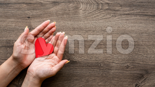Woman is holding a red hearth. Woman hands. Wooden background. Top view Stock Photo