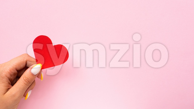 Female hands hold a red heart on pink background. Holiday concept. Front view Stock Photo