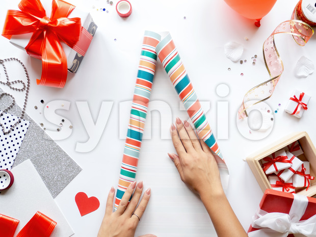 Female hands on table with things for preparing gifts, gift boxes, tapes, stationery. Holiday concept. Top view Stock Photo