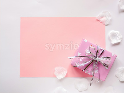 A pink paper sheet and gift box on white background, petals around. Top view Stock Photo