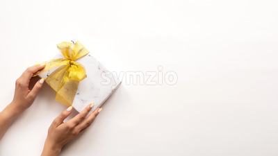 Female hand holds a gift box with golden tape on white background. Holiday concept. Stock Photo