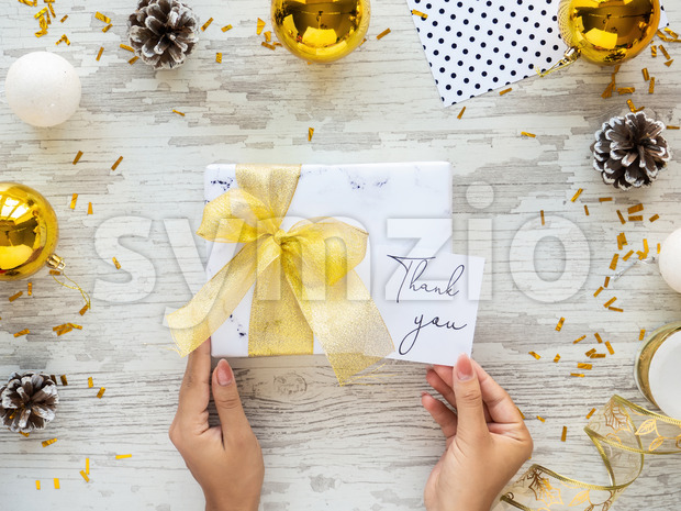 Female hand holds a gift box with golden tape, note with message, Christmas decoration around. Wooden background. Holiday concept. Stock Photo