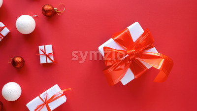 Multiple white gift boxes with red tapes and Christmas decoration on red background. Top view Stock Photo