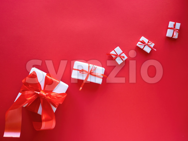 Multiple white gift boxes with red tapes on wooden background. Top view Stock Photo