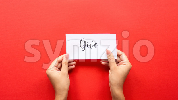 Female hand holds a note with message. Red background. Front view Stock Photo