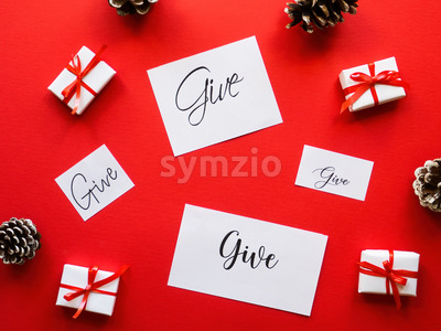 Multiple white gift boxes, notes with messages and fir cones. Red background. Holiday concept Stock Photo