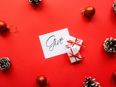 Two white gift boxes, note with message and Christmas decoration. Red background. Holiday concept Stock Photo