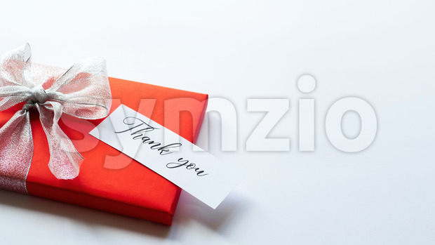 A red gift box with grey tape and a note with message. White background. Holiday concept Stock Photo